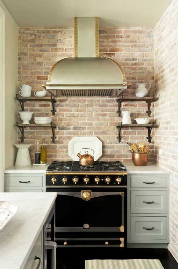 Elegant kitchen with overhead hood, open shelving, and antique brick backsplash