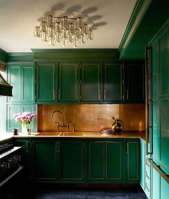Unique polished copper backsplash with emerald cabinets