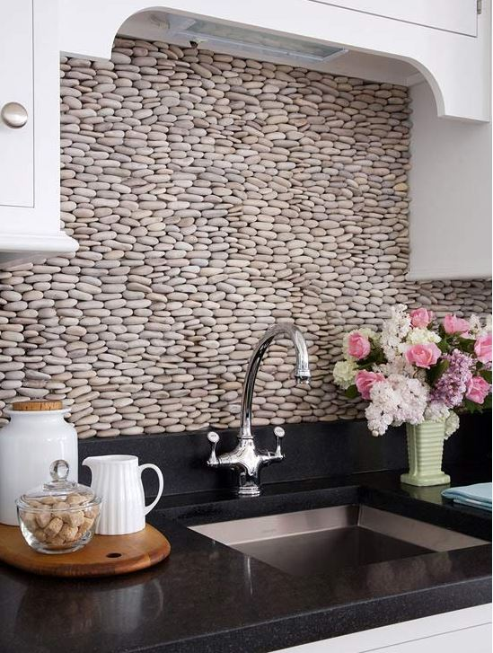 Pebble backsplash in a kitchen with black counterop white cabinets