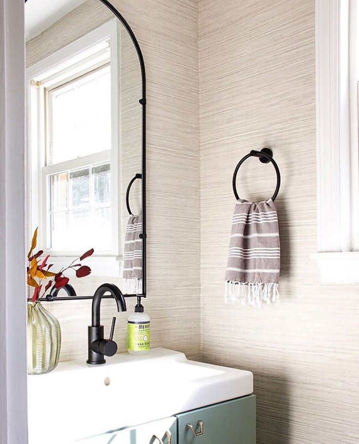 Simple and elegant powder room with grasscloth wallpaper
