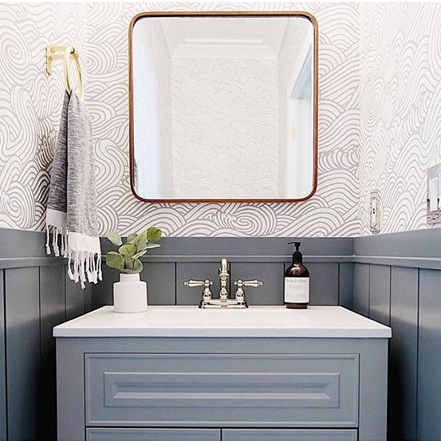 Bold blue and grey powder room featuring graphic wave wallpaper