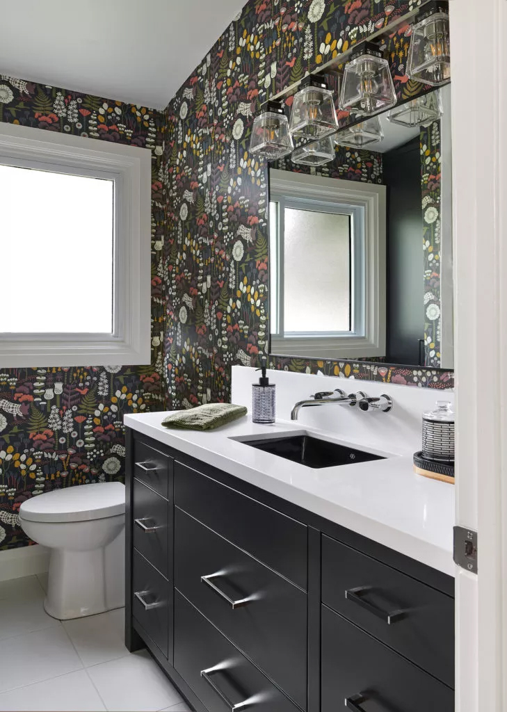 Test out bold design trends in small spaces, like this black bathroom with whimsical woodland wallpaper