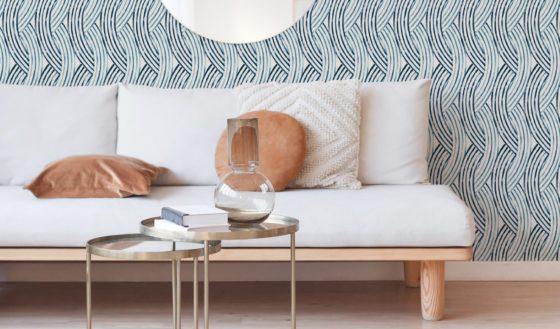 A modern blue geometric wallpaper lies beneath a Scandinavian themed living room