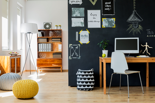 A chalkboard wall is the main focus of this desk/office area. Yellow accents and light wooden furniture is displayed throughout .